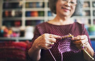 Woman knitting purple material